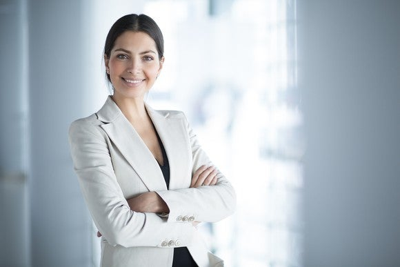 woman in white business suit smiling with arms crossed.