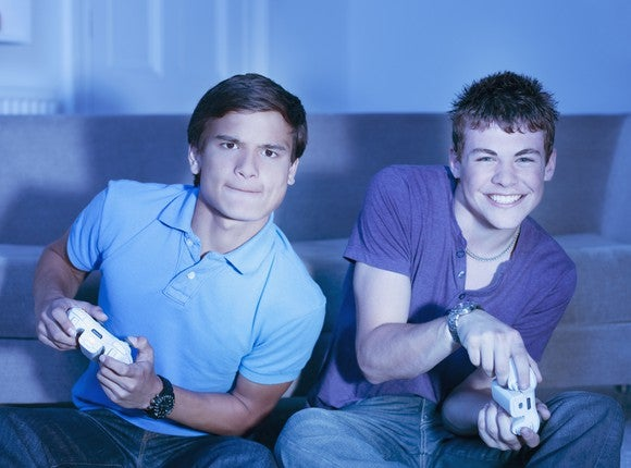 Two young men play a console game.