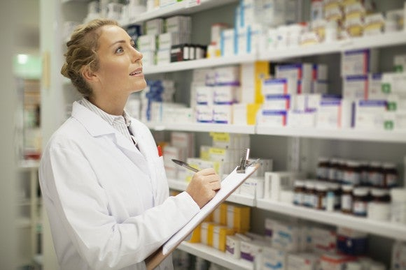 A female pharmacist with a clipboard looking at shelves of medicine.