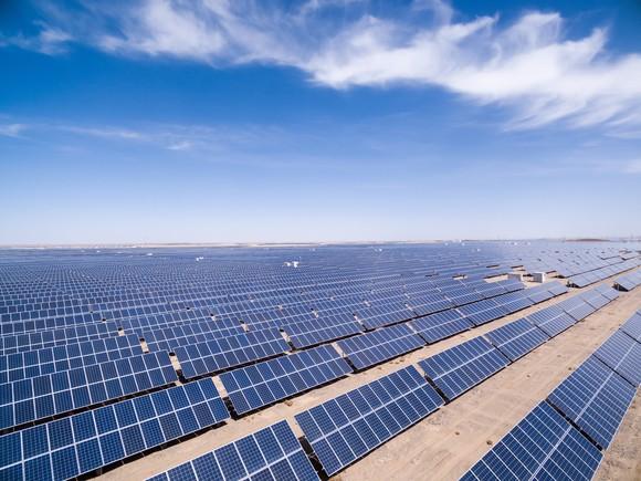 Rows of solar panels at a solar farm in the desert under a blue sky.