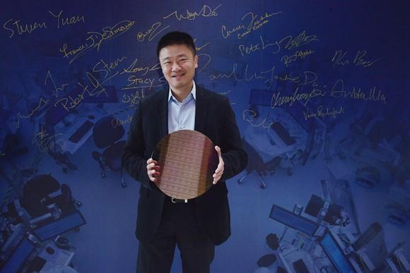 An Arm executive holding an Intel wafer.