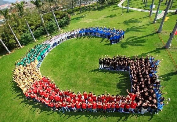 Google employees wearing colored shirts and forming the G logo for Google on a grassy lawn