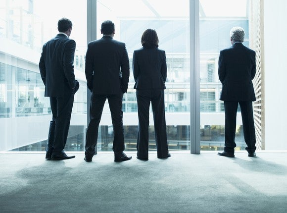Four executives in suits staring out a window
