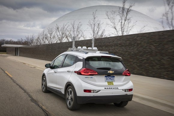 White car on a road with autonomous driving sensors on top of it, in front of a large dome.