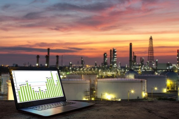 A laptop on a table with a petrochemical complex in the background.