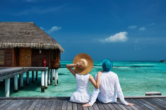 Man and woman seated on a pier look out across the ocean.