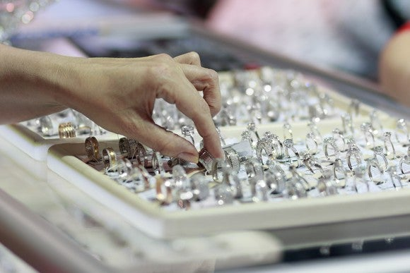 A woman's hand touching a selection of diamond rings