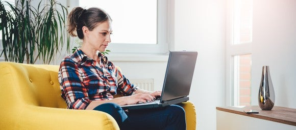 Woman typing on a laptop while sitting on a couch
