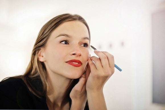 Woman applying eyeliner in front of mirror.