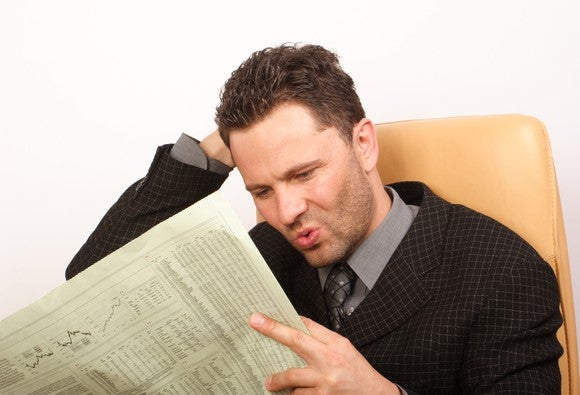 A seated man in a suit reading a financial newspaper, searching for undervalued stocks with his mouth puckered.