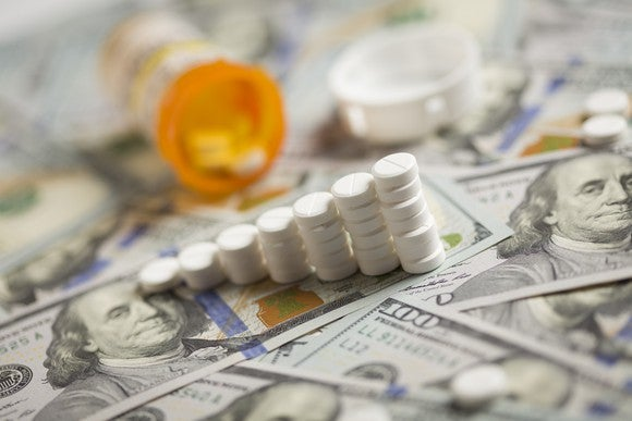 An ascending stack of prescription pills lying atop a messy pile of hundred dollar bills.
