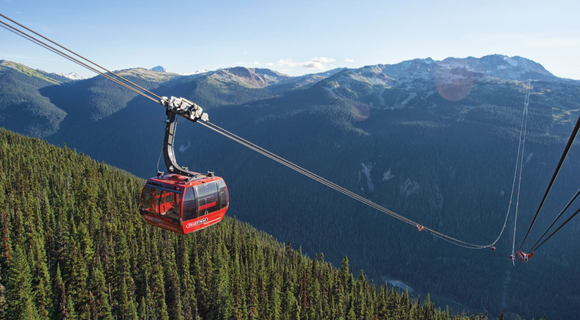 Red cable car going up the side of a mountain with evergreen pine trees, with a snow-capped mountain range in the background.