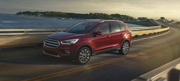 A red 2018 Ford Escape, a compact crossover SUV, on a waterfront road.