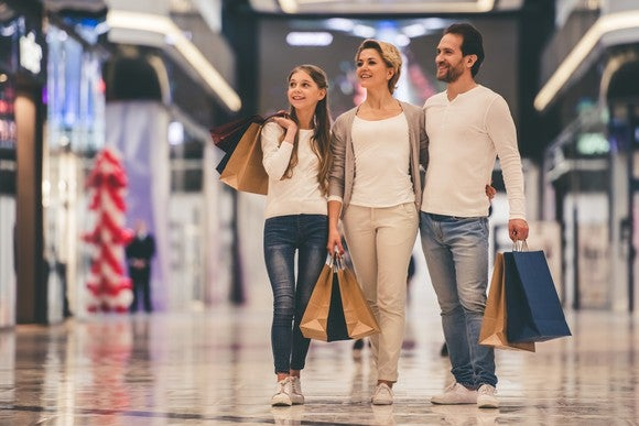 Family of three shopping in a mall.