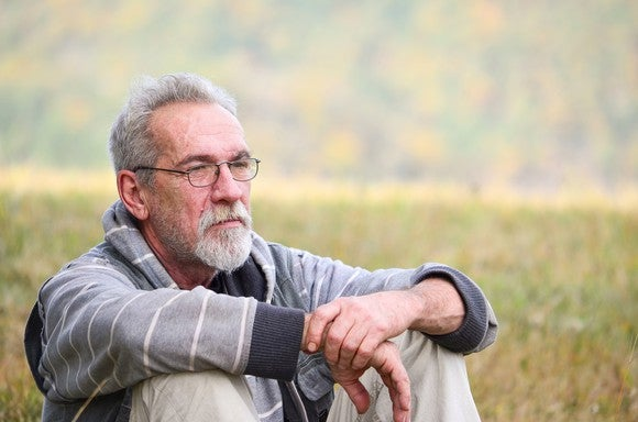 Older man with a concerned expression sitting in a field