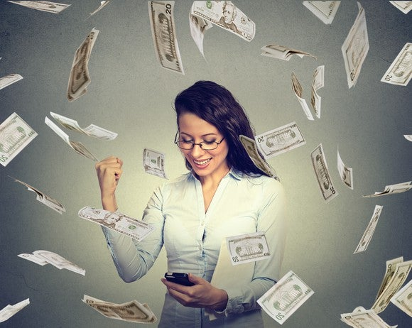 A woman checking her phone and pumping her fist in excitement while $20 bills fall around her.