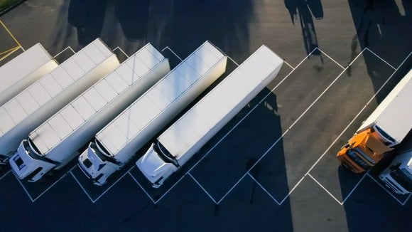 A bird's-eye view of several semi trucks parked at a rest stop.