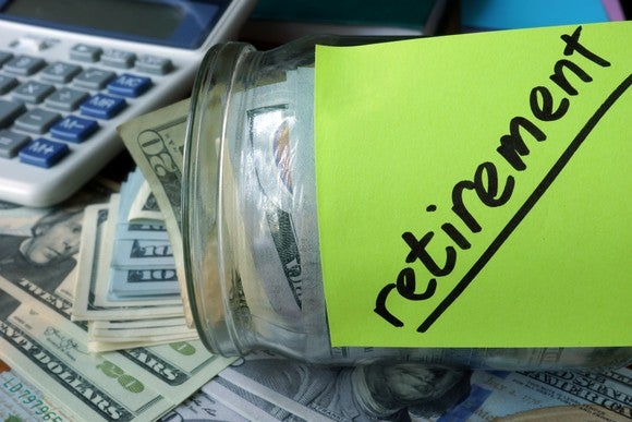 Glass jar holding cash with green sticky note with word Retirement written on it, next to a calculator.