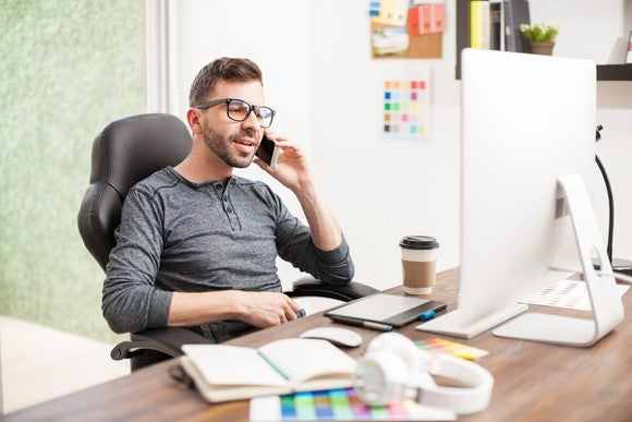 Man at a desk talking on a mobile phone