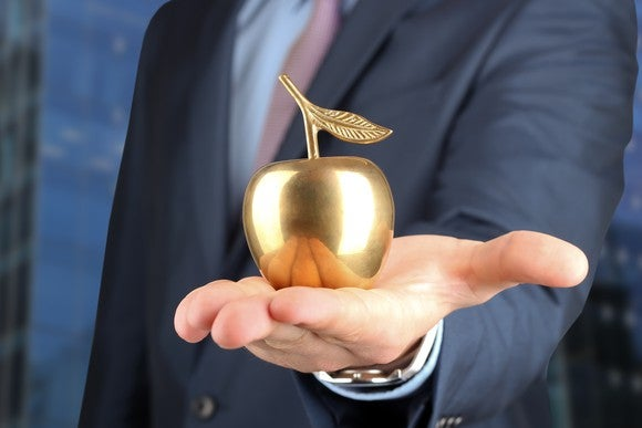 Businessman holding up a golden apple in the palm of his outstretched hand.