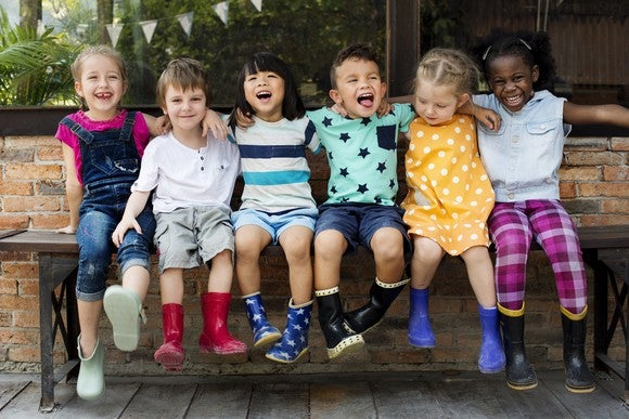 Six kids sitting on a bench smiling and laughing.