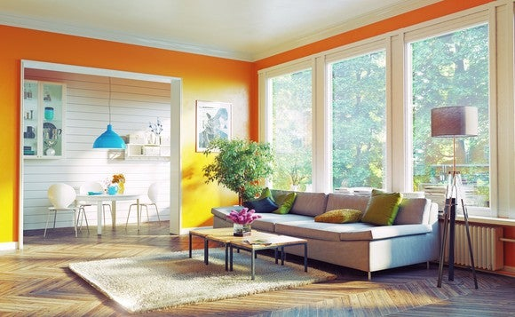 A living room furnished in modern style with orange walls, a couch, and a coffee table.