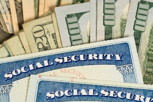 Two Social Security card lying on a fanned pile of cash bills.