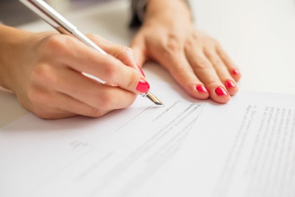A person with red nail polish on signs a paper with a fountain pen.