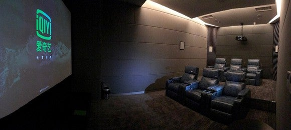 iQiyi's new Yuke-style on-demand cinema with two rows of tiered recliners and a projector showing on a large screen.