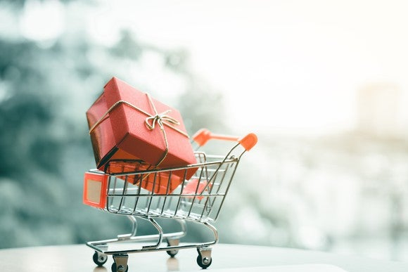 A miniature shopping cart with a wrapped gift inside.