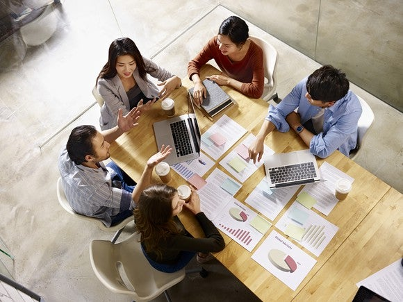 An overhead view of five people sitting around a table that's covered in papers, two laptops, and coffee cups.