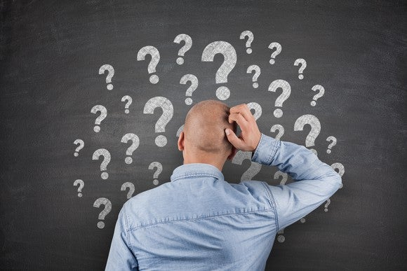 Man scratching his head in front of question marks on a blackboard.