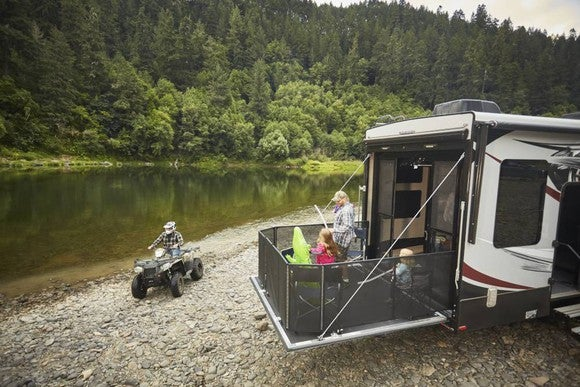 Family enjoying activities on camper parked by a riverside.