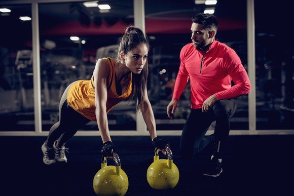 A fitness coach helping a woman train with kettlebells.