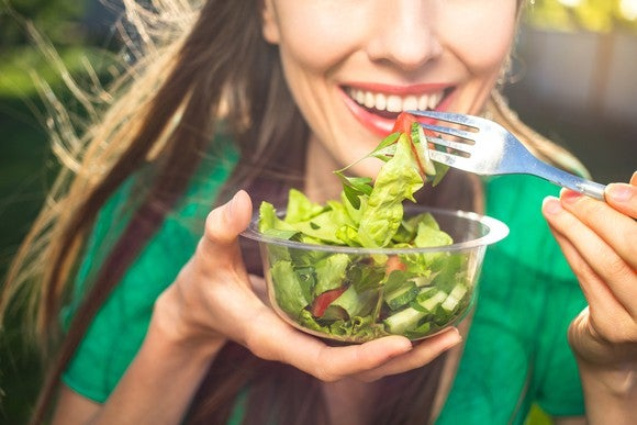 Close-up of woman eating green salad with a fork from a glass bowl.