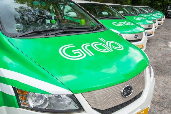 A line of small vehicles painted in Grab's green-and-white color scheme.