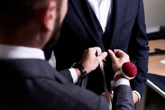 A tailor fitting a man for a suit