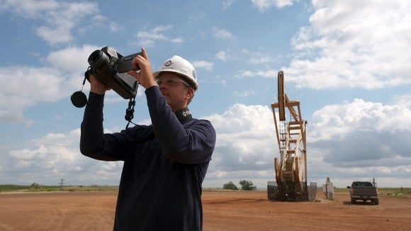 Man in hard hat and safety glasses with handheld monitoring device in front of a pumping oil well.