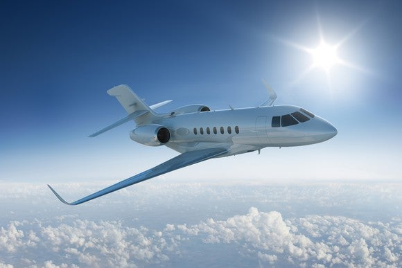 Corporate jet flying above clouds