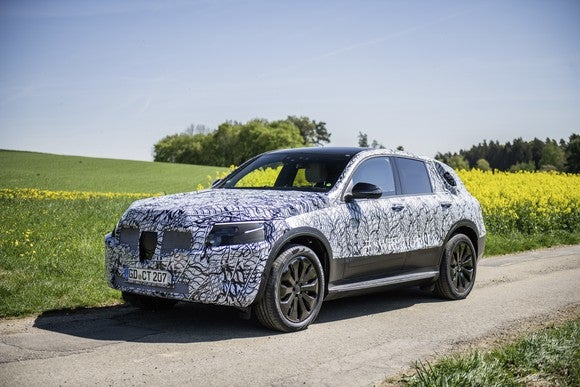 The Mercedes-Benz EQA, a compact electric SUV, shown wrapped in black and white camouflage and parked next to a field.
