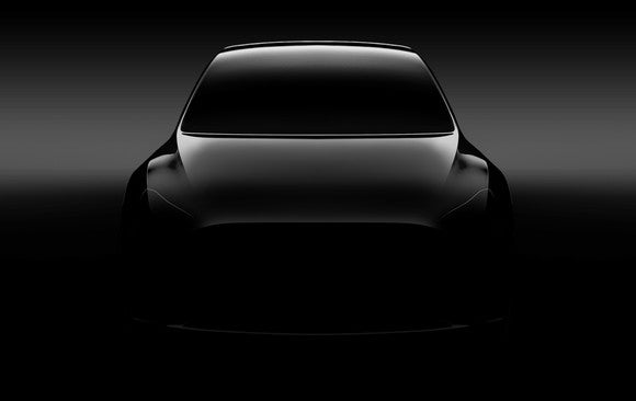 """A """"teaser"""" photo of a silver Tesla Model Y, a sleek SUV, viewed from the front."""