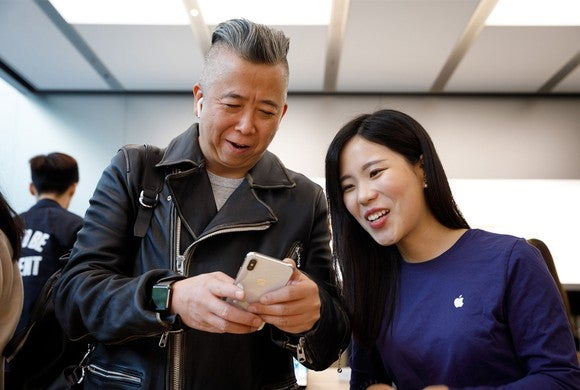 A customer holding a new iPhone X at an Apple Store in China