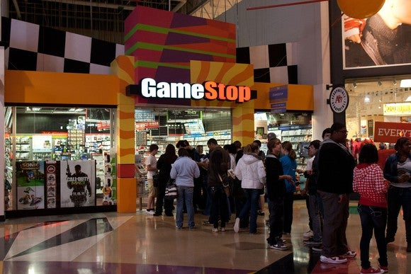 Shoppers lining up outside a GameStop before a midnight release party.