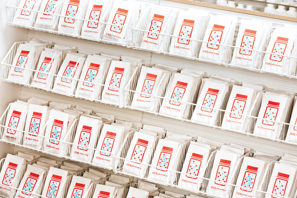 Wall display with prescription bags that have CVS labeling on them.
