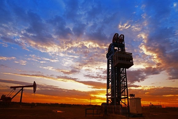 An oil drilling rig and oil pump sunset.