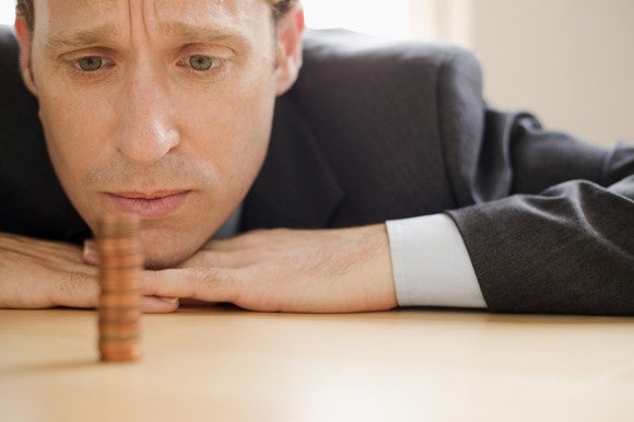 A businessman pensively looking at a single stack of pennies on a table.