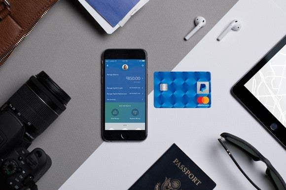 The PayPal-branded credit card on a desk next to a phone with the PayPal app, a passport, camera, earbuds, and sunglasses.