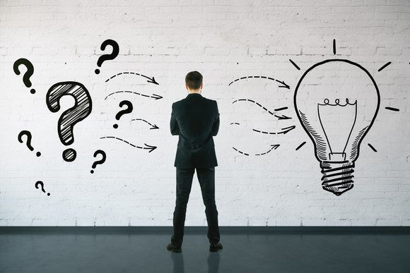 A man wearing a suit staring at a wall with question marks and a light bulb drawn on it.