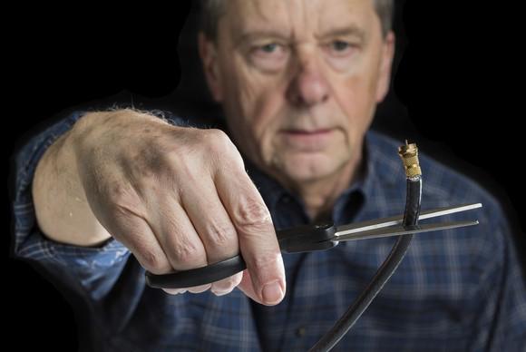 A man cuts a coaxial cable.