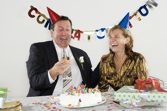 Two middle aged people sitting behind a retirement party cake, wearing party hats and smiles